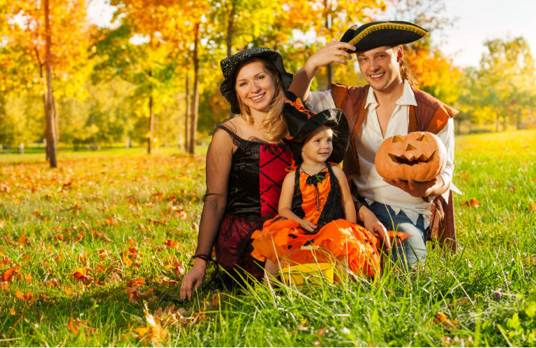 family in Halloween costumes posed with jack-o-lanterns