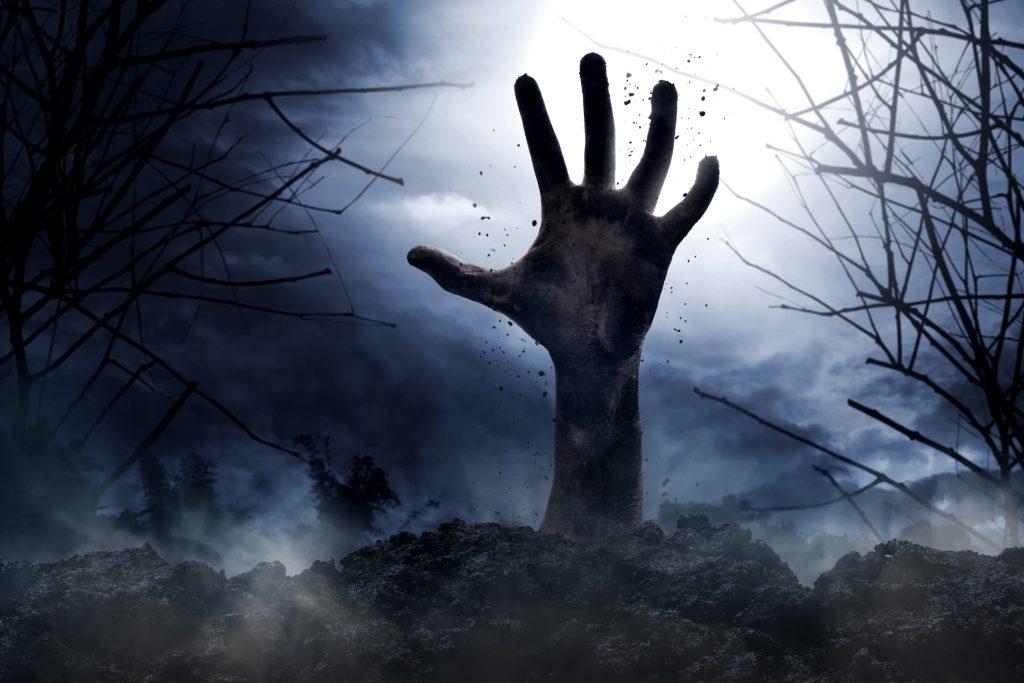 Zombie hand rising from the ground at night