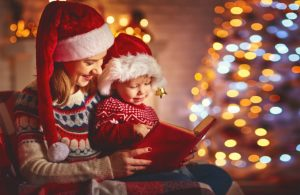 mom reading a Christmas story to her son by a Christmas tree