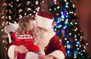 little girl whispering to Santa Claus by Christmas trees