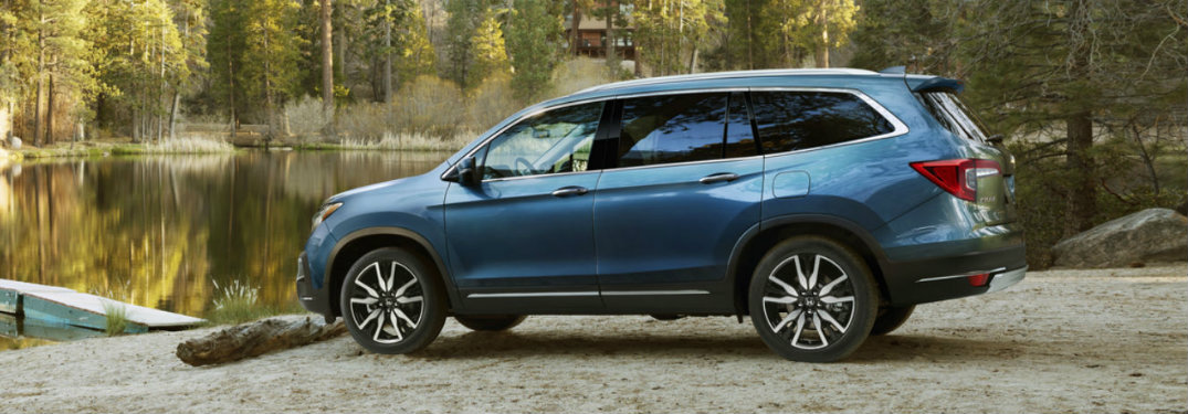 side-profile-of-blue-2019-Honda-Pilot-parked-by-quiet-river