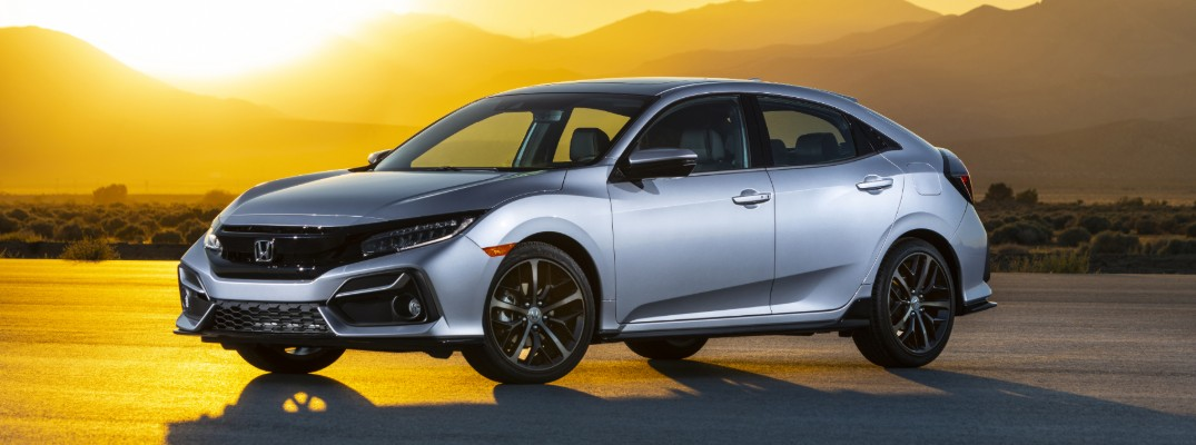 2020 Honda Civic Hatchback Sport Touring with Lunar Silver Metallic paint color parked on an asphalt plain in the desert as a bright and big sun begins to set