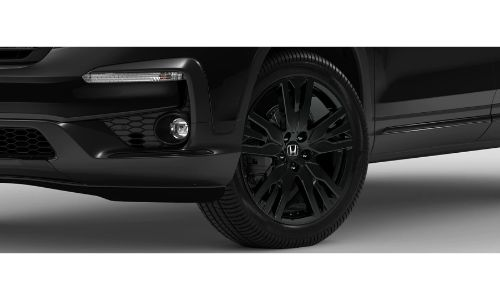 2020 Honda Pilot Black Edition exterior closeup of front bumper, tire, and wheel design with Crystal Black Pearl color