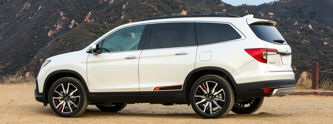 2020 Honda Pilot Elite exterior side shot with platinum white pearl paint color parked on a sand gravel terrain near grassy mountains