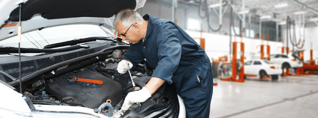 a service technician mechanic in a jumpsuit working under a vehicle's hood performing automotive service inside a dealership's service department garage