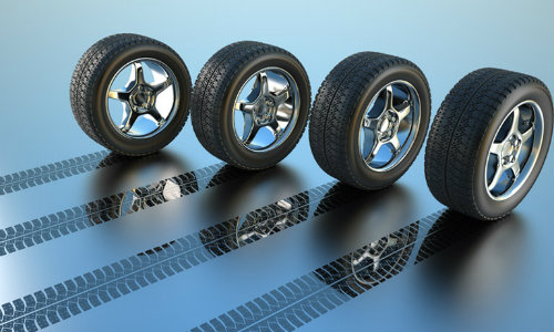 a line of tires rolling and leaving their tread marks printed on the clear, blue floor
