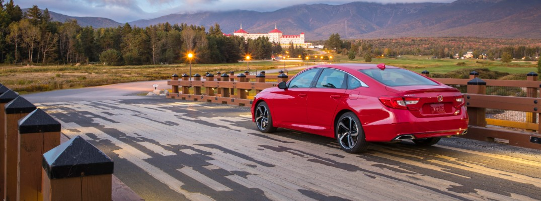 2020 Honda Accord Sedan exterior rear side shot with san marino red paint color parked near a wooden fence on the approach to an old manor in a mountain forest