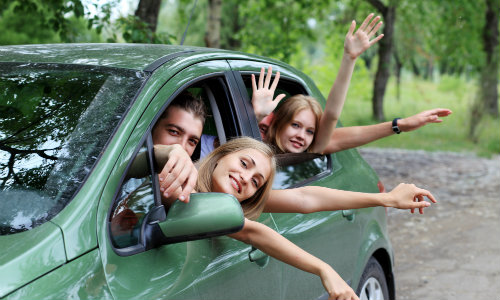 a family waving out of the windows of a green SUV driving through a forest