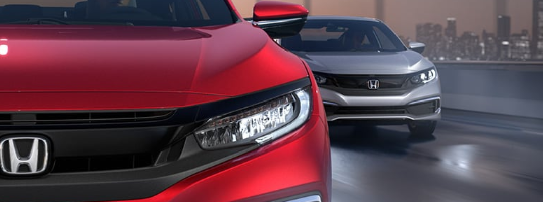 2020 Honda Civic models in Rallye Red and Lunar Silver Metallic driving down a highway at night