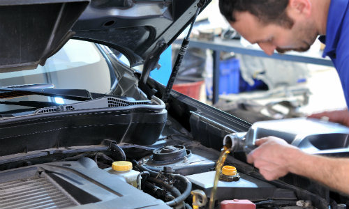 a mechanic in an auto garage pouring in new fluid as part of an oil change