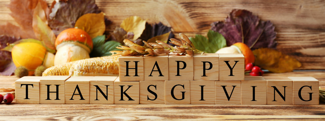Happy Thanksgiving written out in wooden building blocks in front of a fall decoration of farm crops and vegetables