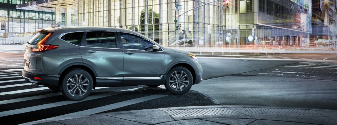 2020 Honda CR-V Touring exterior side shot with gray paint color parked at an intersection at night in a busy city of lights