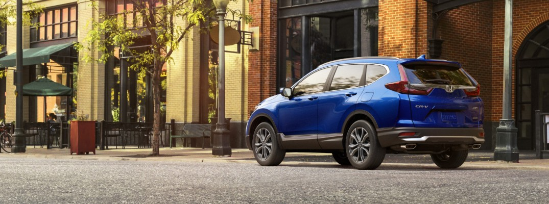 2020 Honda CR-V Touring with Aegean Blue Metallic paint color exterior rear shot parked on a gravel rock road near cafes and lampposts