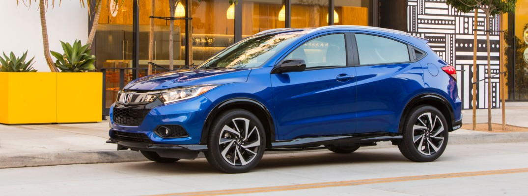 2020 Honda HR-V Sport exterior shot with Aegean Blue Metallic paint color parked on the curb outside a luxury cafe with flora and fauna