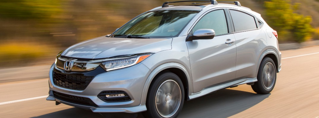 2020 Honda HR-V Touring exterior closeup in silver gray paint color speeding down a country road near grassy hills