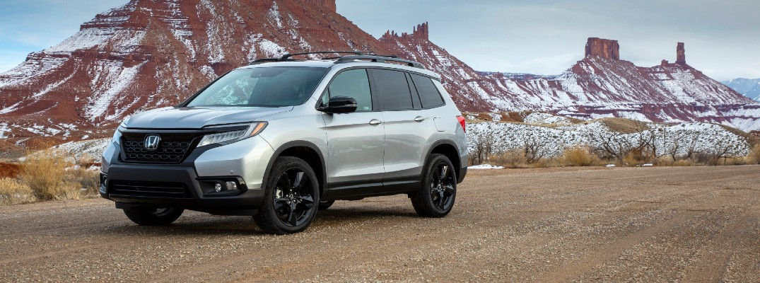 2020 Honda Passport exterior side shot with lunar silver metallic paint color parked near snow-capped mountain cliffs
