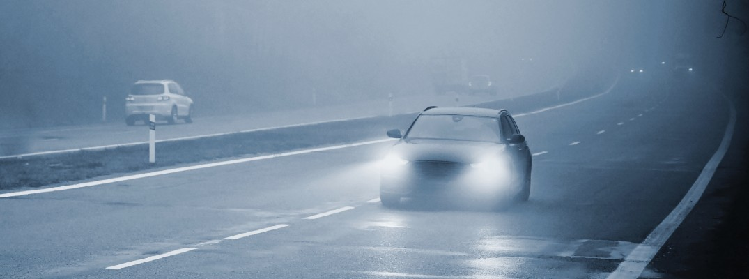 cars driving on the highway within a heavy fog during winter