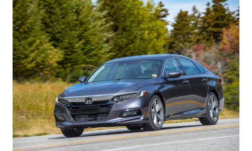 2020 Honda Accord Touring sedan exterior shot with gray metallic paint color driving near a forest