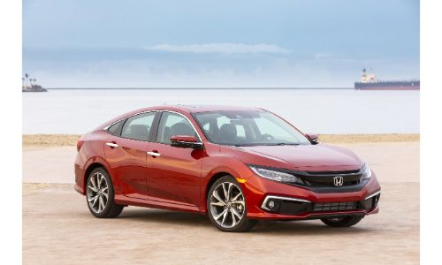 2020 Honda Civic Touring Sedan exterior shot with red painr color parked on a sandy beach