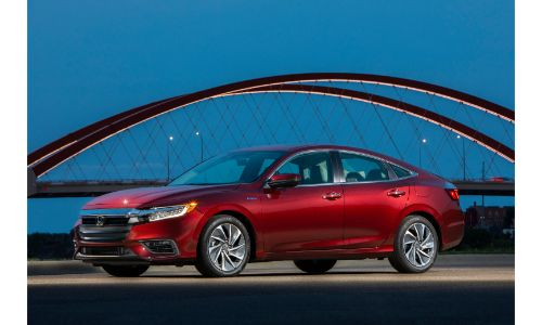 2020 Honda Insight exterior side shot with red paint color parked near an arch bridge with a dark blue sky
