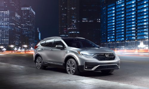 2020 Honda CR-V Touring exterior shot with gray silver paint color parked on the side of a street in a city at night