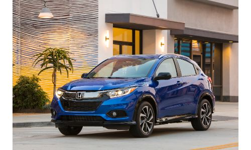 2020 Honda HR-V Sport exterior shot with Aegean Blue Metallic paint color parked outside a luxury palm cafe
