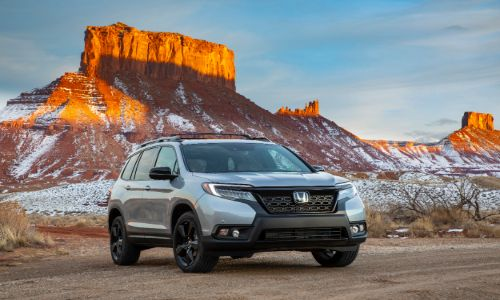 2020 Honda Passport exterior shot with gray silver paint color parked in a desert with an orange mountain background