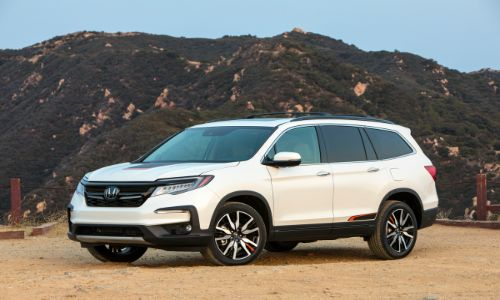 2020 Honda Pilot Elite exterior side shot with white paint color parked on a dirt plain near grassy hills