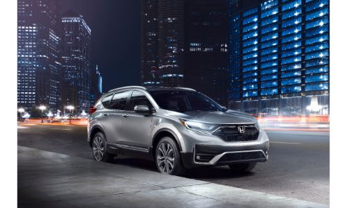2020 Honda CR-V Touring exterior shot with silver gray paint color parked on the side of a city street at night
