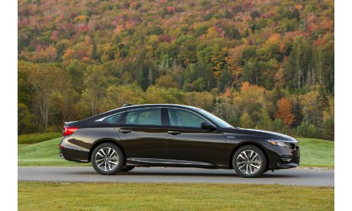 2020 Honda Accord Hybrid with crystal black pearl paint color exterior side shot parked outside of a forest