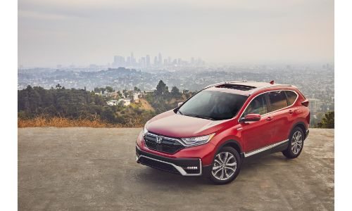 2020 Honda CR-V Hybrid exterior shot with red paint color parked on a cliff with a city skyline in a foggy background