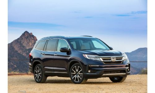 2021 Honda Pilot Elite exterior shot parked on a cliff of yellow dirt with mountains in the background