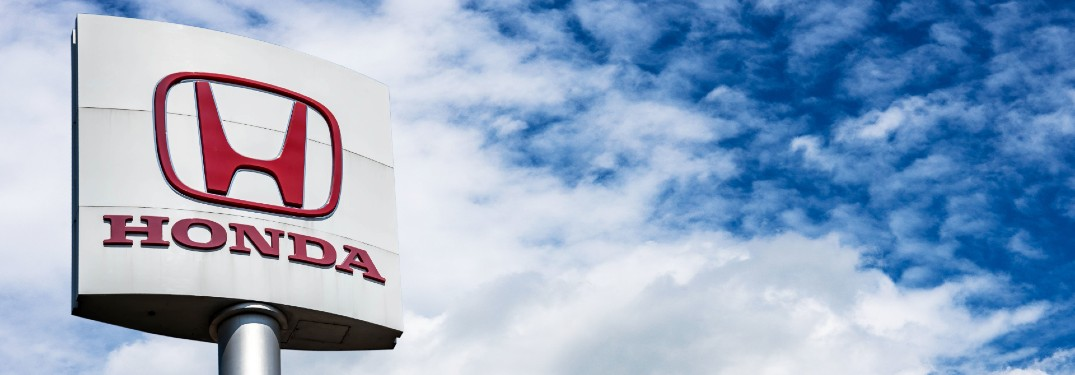 Honda automotive store sign with a red brand logo against a cloudy blue sky