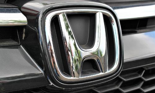 closeup of Honda logo emblem on a car exterior above a mesh grille