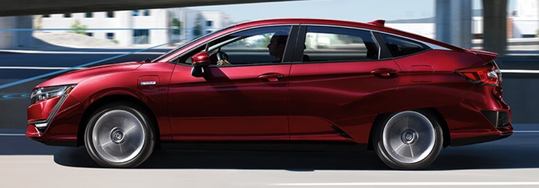 2021 Honda Clarity Plug-In Hybrid exterior side shot with Crimson Pearl paint color driving on a highway
