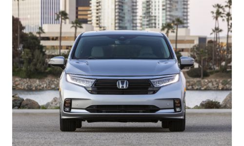 2021 Honda Odyssey exterior front shot with Lunar Silver Metallic paint color parked in front of skyscrapers