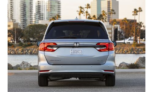 2021 Honda Odyssey exterior rear shot with Lunar Silver Metallic paint color parked in front of skyscrapers
