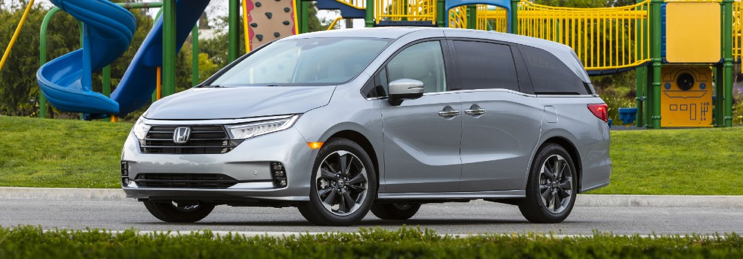 2021 Honda Odyssey exterior shot with Lunar Silver Metallic paint color parked in front of a children's playground park