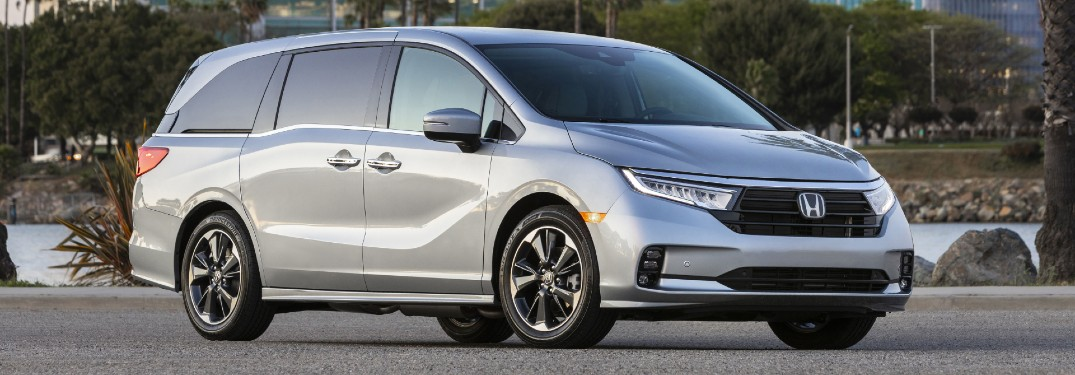 2021 Honda Odyssey exterior shot with Lunar Silver Metallic paint color parked on an empty lot near palm trees