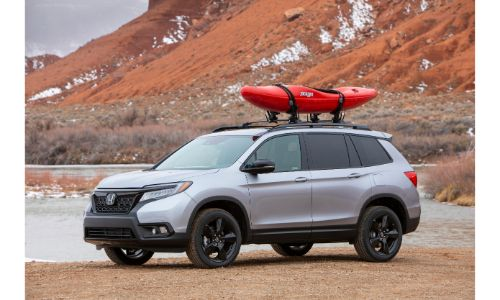2021 Honda Passport exterior shot with Lunar Silver Metallic paint color parked on a beach near water and mountains with a red kayak on its roof rails
