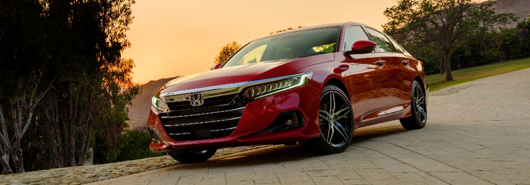 2021 Honda Accord Hybrid exterior shot with San Marino Red paint color option parked on a stone tile path with a sunset in the background sky