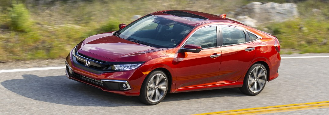 2021 Honda Civic Touring Sedan exterior shot with Molten Lava Pearl paint color driving on a country highway near grassy hills
