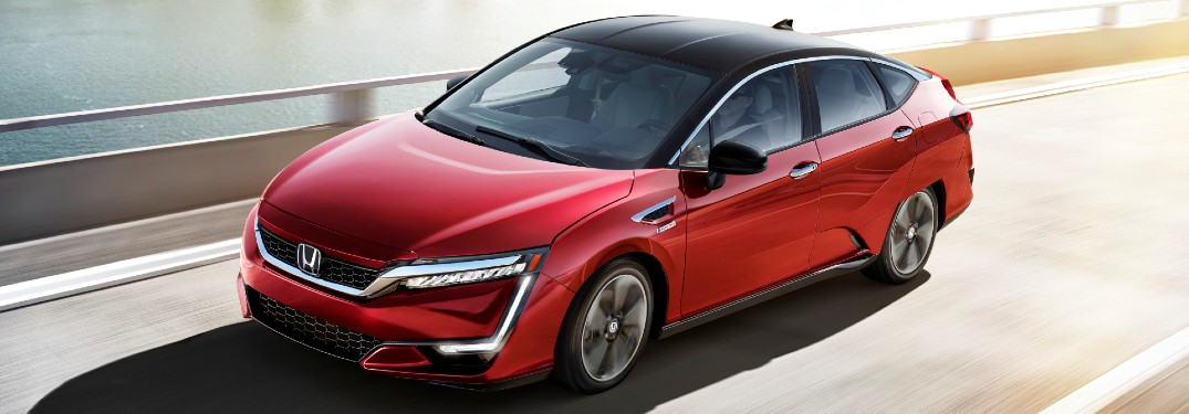 2021 Honda Clarity Fuel Cell exterior shot with Crimson Pearl paint color driving on a highway bridge over water