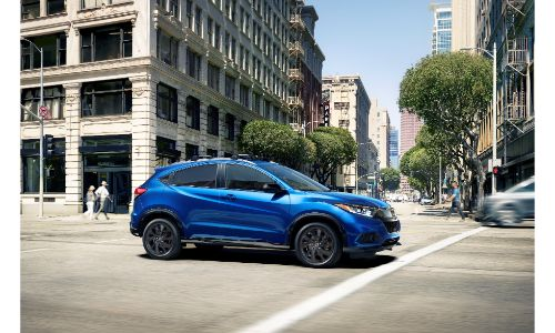 2021 Honda HR-V exterior shot with blue paint color driving through a city during the daytime