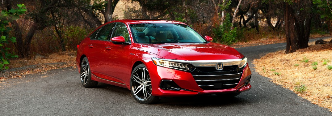 2021 Honda Accord Hybrid exterior shot with red paint color parked on an asphalt road in a forest