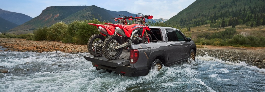 2021 Honda Ridgeline with HPD Package exterior rear shot with motorbikes in its truck bed driving out of water onto a beach of rocks and gravel