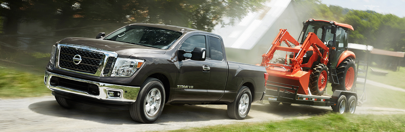 silver nissan titan truck towing a tractor
