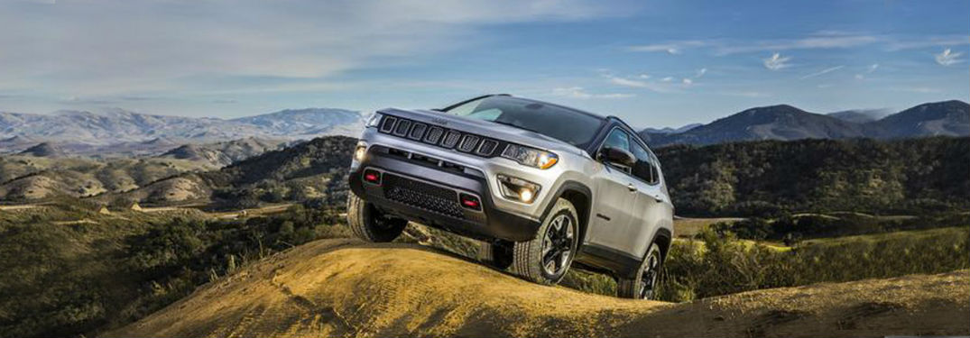 Front exterior view of a gray 2018 Jeep Compass perched on a hilltop