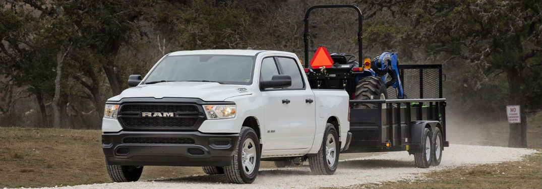 Front driver side exterior view of a white 2019 Ram 1500 hauling large farm equipment