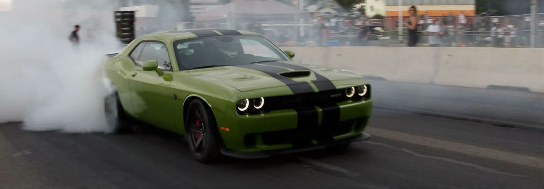Front passenger side exterior view of a green 2019 Dodge Challenger doing a burnout